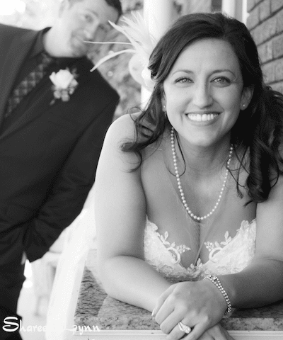Black and white photo bride on a dresser groom in the background
