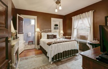 Luscious brown walls with a white iron bed with a soft turquoise spread along crisp white window curtains.
