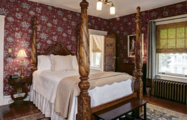 Colonial French large four-poster bed with a white spread and red flowered wallpaper